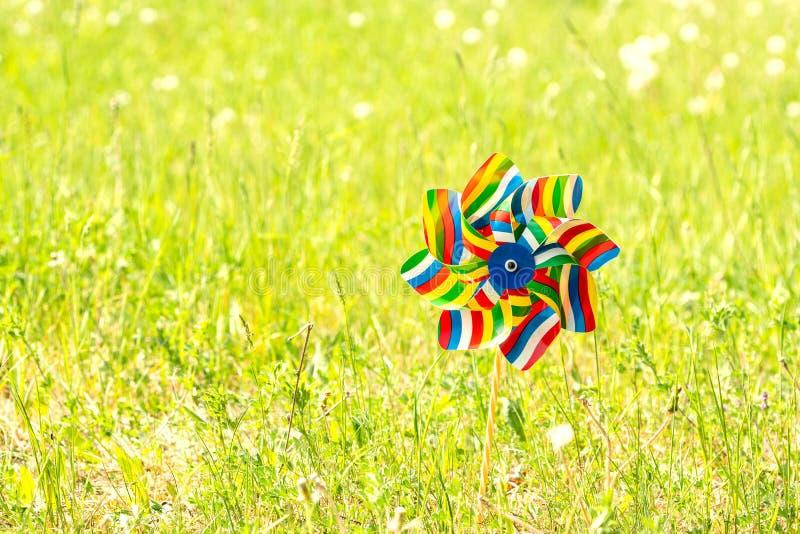Molinillo de viento colorido en el prado del verano fotografía de archivo