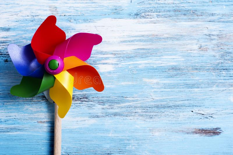 Molinillo de viento colorido en una superficie de madera azul foto de archivo libre de regalías