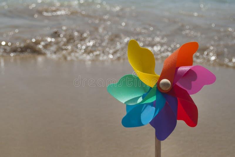 Molinillo de viento colorido giratorio del arco iris en la playa imagen de archivo libre de regalías