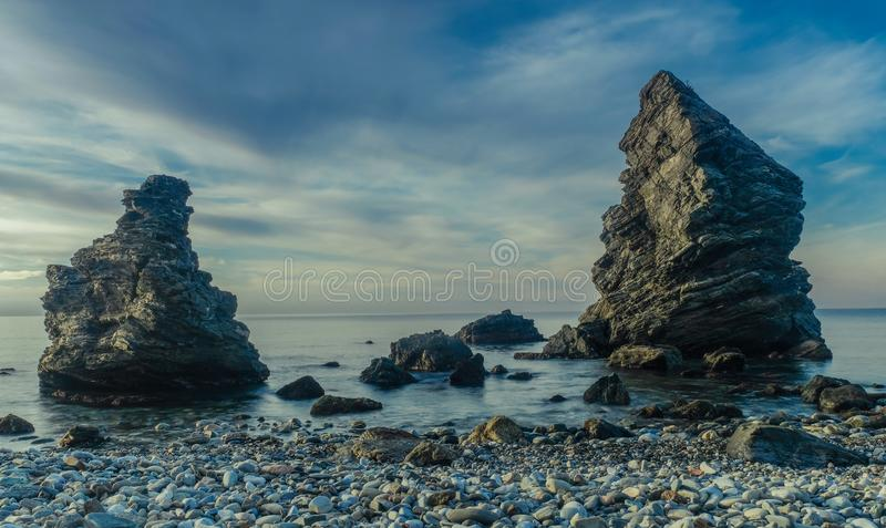 Molino Beach in Spain. Nerja, Malaga, Andalusi, Spain - February 4, 2019: Molino Beach, small stone beach with two large rocks on the shore, Nerja, southern royalty free stock images