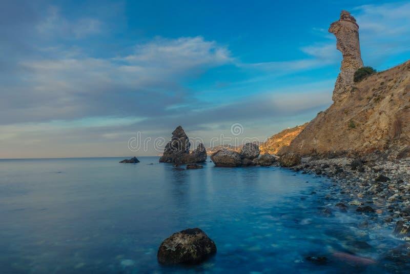 Molino Beach with old rocks. Nerja, Malaga, Andalusi, Spain - February 7, 2019: Playa del Molino, small stone beach with three large rocks on the shore, Nerja royalty free stock image