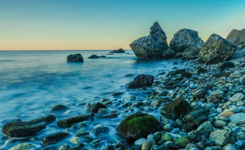 Molino Beach, southern Spain. Nerja, Malaga, Andalusi, Spain - February 4, 2019: Playa del Molino, small stone beach with three large rocks on the shore, Nerja stock photo