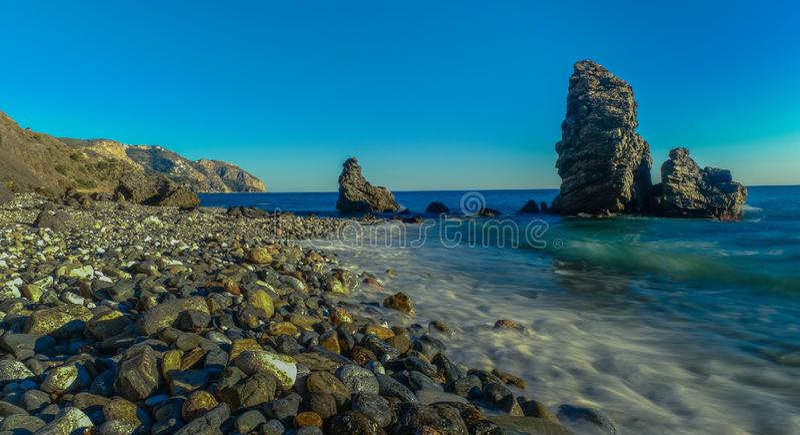 Molino Beach, Spain. Nerja, Malaga, Andalusi, Spain - February 3, 2019: Playa del Molino, small stone beach with three large rocks on the shore, Nerja, southern stock photo