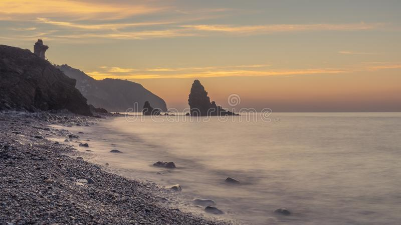 Molino beach, Spain. Nerja, Malaga, Andalusi, Spain - February 10, 2019: Playa del Molino, small stone beach with three large rocks on the shore, Nerja, southern royalty free stock photo
