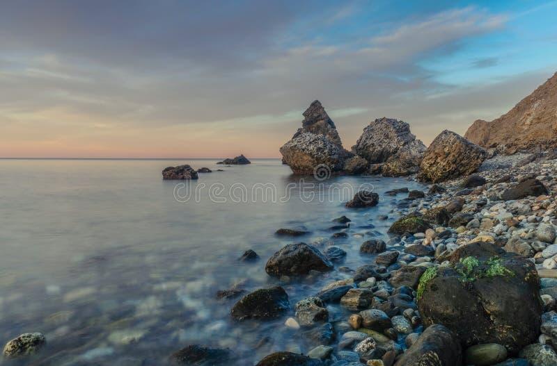 Molino Beach, the stone beach. Nerja, Malaga, Andalusi, Spain - February 7, 2019: Playa del Molino, small stone beach with three large rocks on the shore, Nerja royalty free stock photos