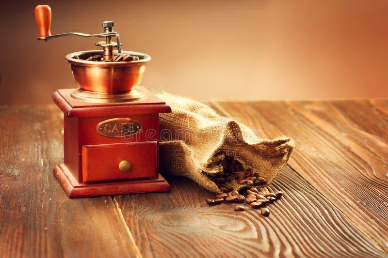 Molino de café con el saco de la arpillera por completo de granos de café asados foto de archivo