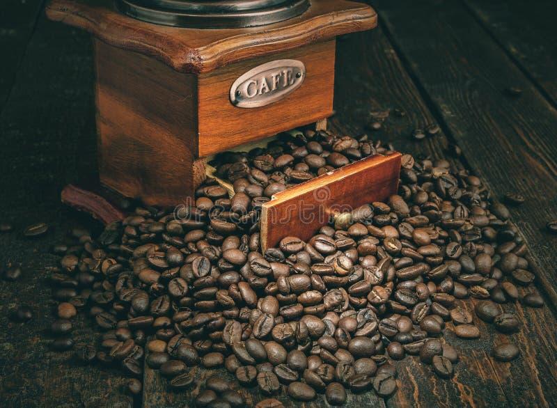 Molino de café con los granos de café en fondo oscuro retro imágenes de archivo libres de regalías