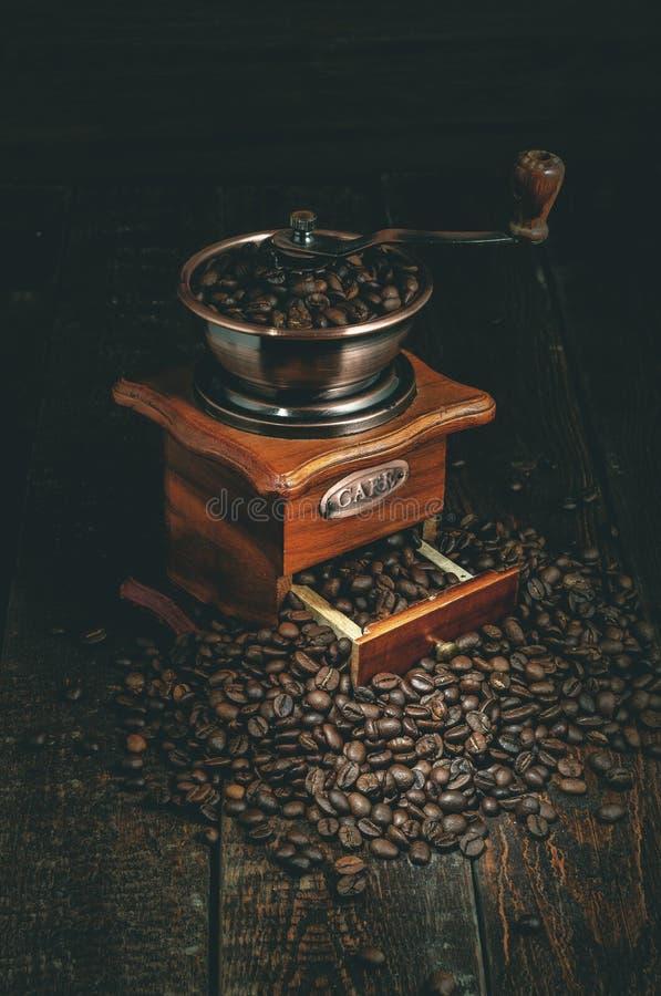 Molino de café con los granos de café en la tabla oscura Fondo retro fotografía de archivo