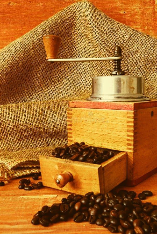 Molino de café del vintage y granos de café en fondo de madera fotografía de archivo