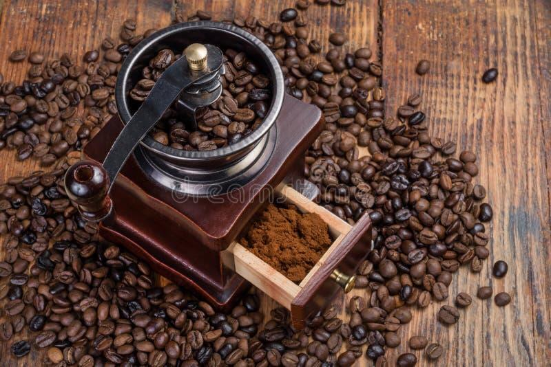 Molino de café en fondo de madera rústico del tablón y granos de café asados fotografía de archivo