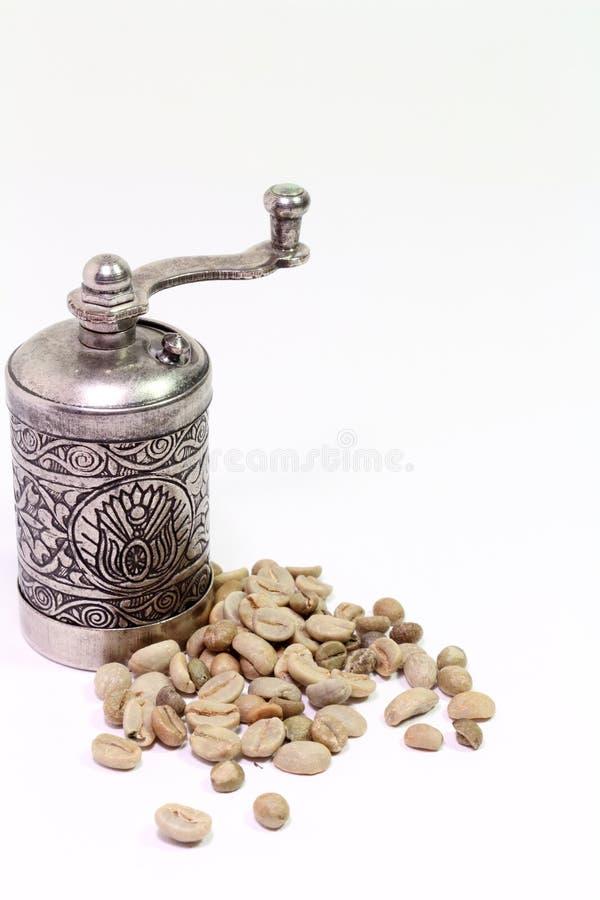 Molino de café oriental árabe con los granos del café verde en el fondo blanco imagenes de archivo