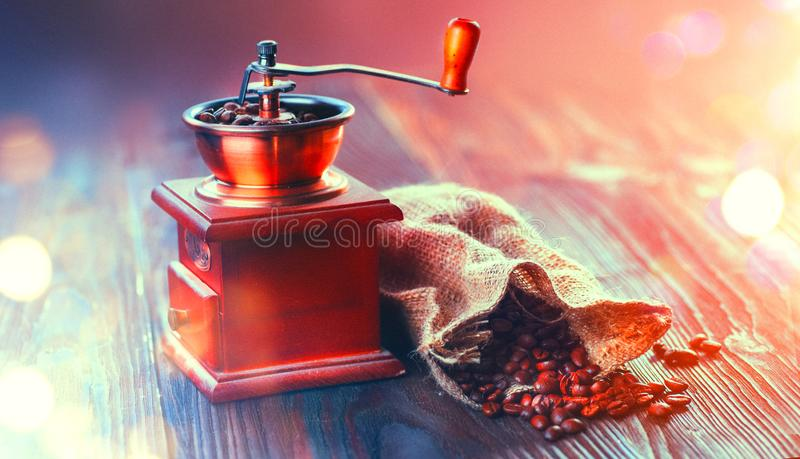 Molino de café y granos de café asados Amoladora de café con el saco de la arpillera por completo de habas asadas sobre la tabla  imagen de archivo libre de regalías