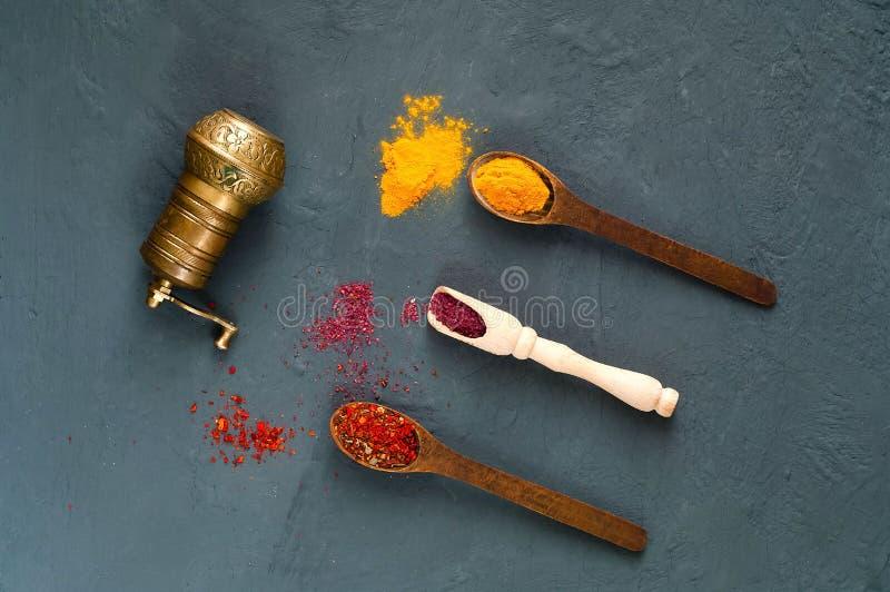 Molino de mano y cucharas de madera con las especias en un fondo oscuro El concepto de comida vegetariana, dieta sana, opción de  imagen de archivo libre de regalías