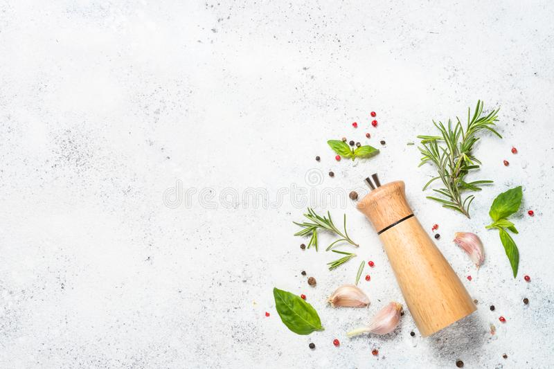Molino de pimienta con las hierbas frescas en blanco foto de archivo