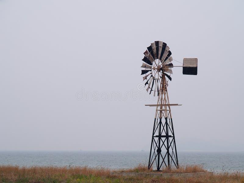 Molino de viento antiguo por el mar imagen de archivo libre de regalías
