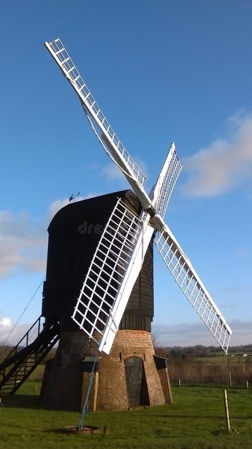 Molino de viento de los posts del inglés con la falda del ladrillo, visión #1 imagenes de archivo