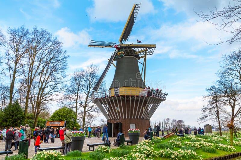Molino de viento en el jardín y los turistas de la primavera alrededor fotos de archivo