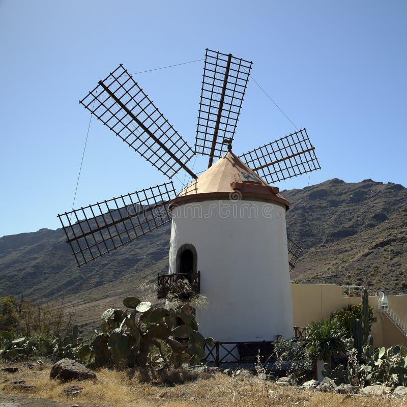 Molino de viento en Gran Canaria, Canarias debajo de la bandera española fotos de archivo