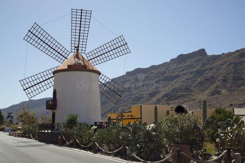 Molino de viento en Gran Canaria, Canarias debajo de la bandera española imagen de archivo libre de regalías