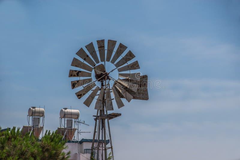 Molino de viento en un ambiente de la ciudad con el cielo azul fotografía de archivo libre de regalías
