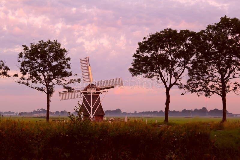 Molino de viento holandés en la salida del sol fotos de archivo
