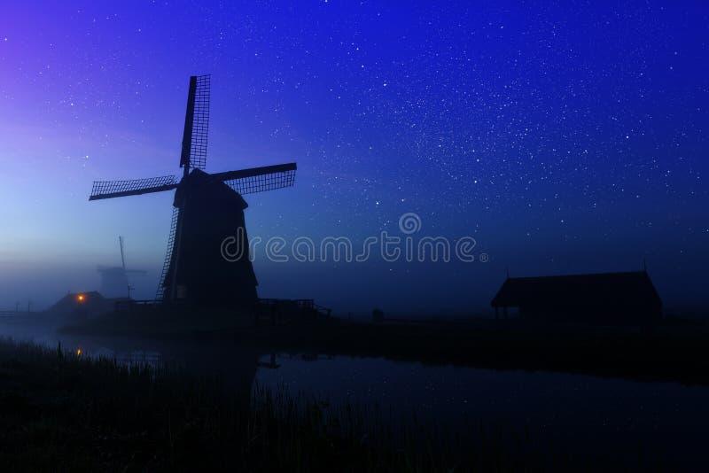 Molino de viento holandés tradicional en noche estrellada Los Países Bajos fotografía de archivo