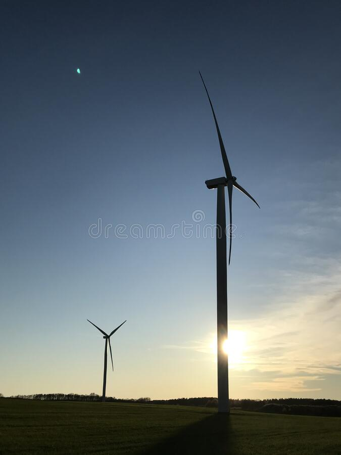Molino de viento o turbina eólica con el sol de puesta detrás y espacio de copia imagen de archivo