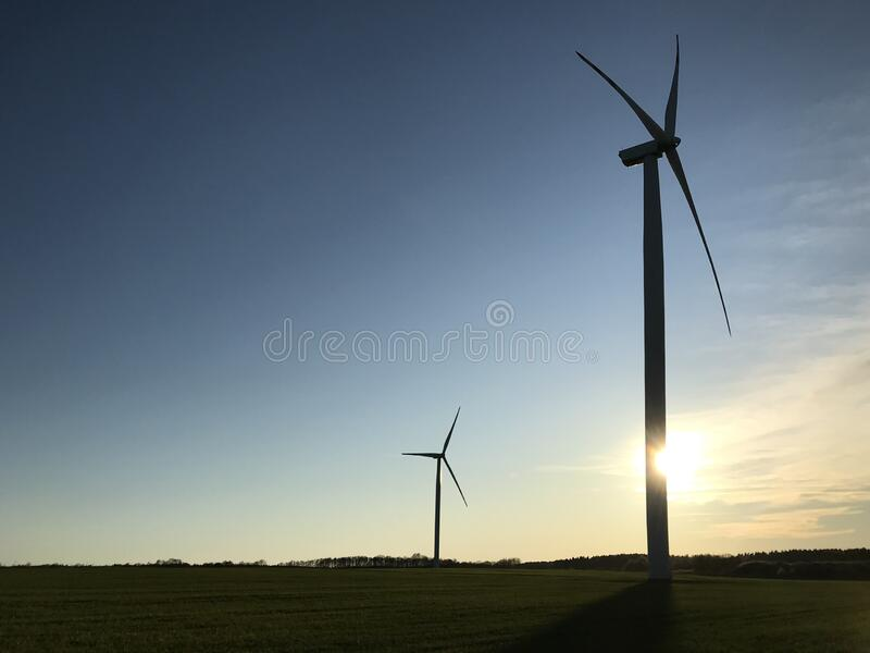 Molino de viento o turbina eólica con el sol de puesta detrás y espacio de copia imagen de archivo libre de regalías