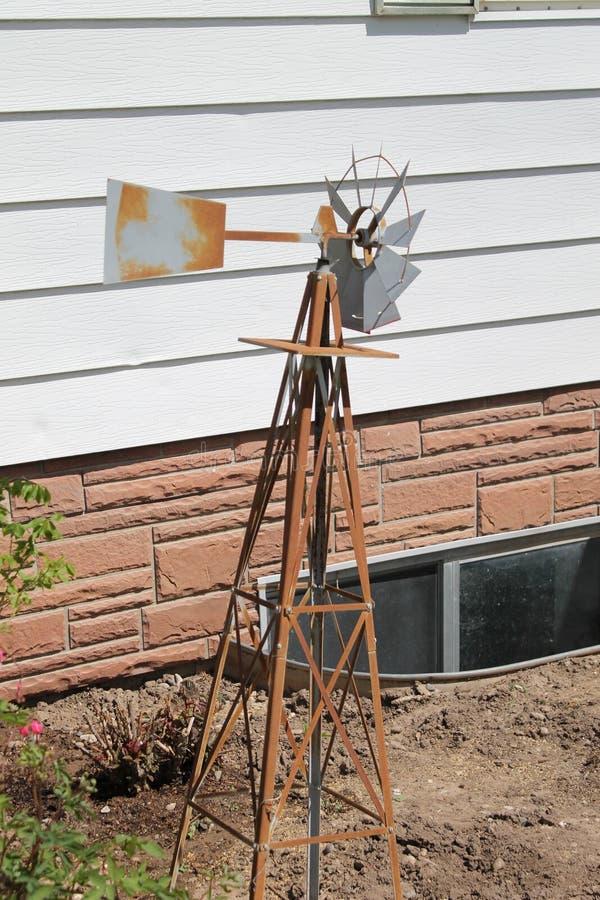 Molino de viento oxidado hacia fuera en la yarda foto de archivo libre de regalías