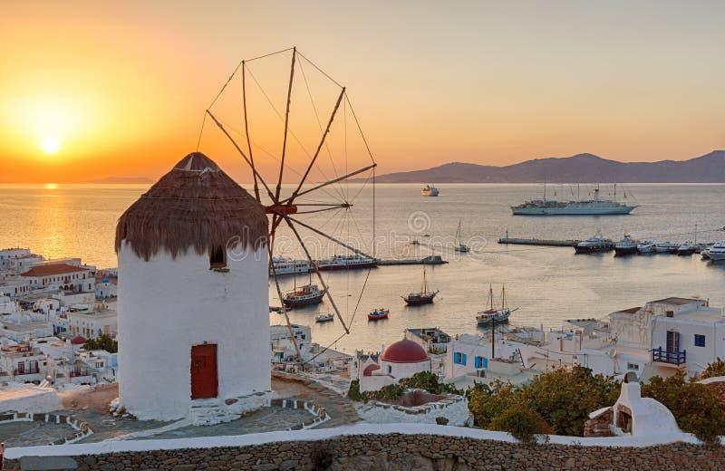 Molino de viento tradicional sobre la ciudad de Mykonos en la puesta del sol fotografía de archivo libre de regalías