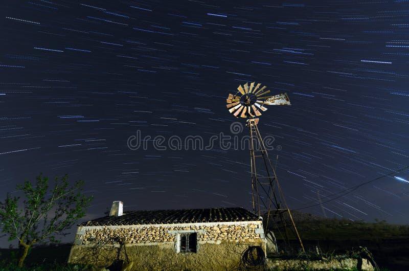 Molino de viento viejo de la granja para el agua de bombeo con las cuchillas de giro fotos de archivo