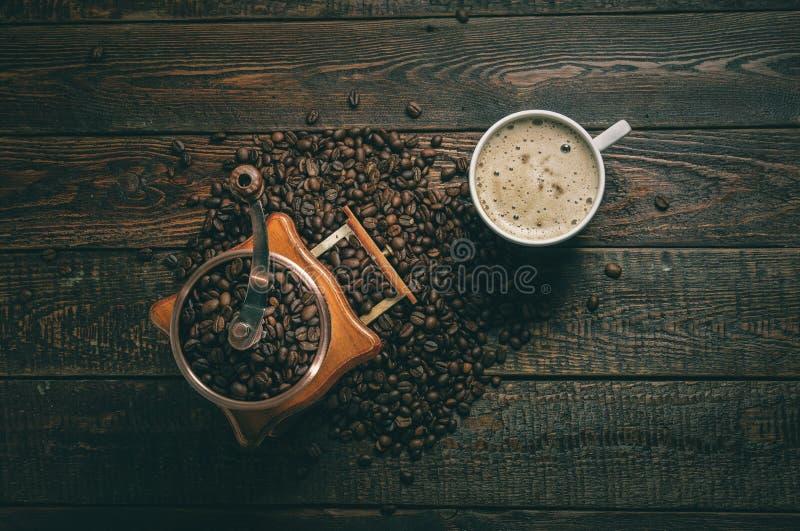 Molino y taza de café con las habas en fondo oscuro Visión superior fotos de archivo