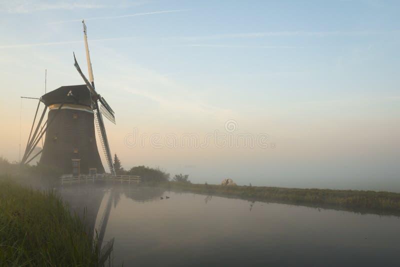 Molinoes de viento de niebla en un dique imágenes de archivo libres de regalías