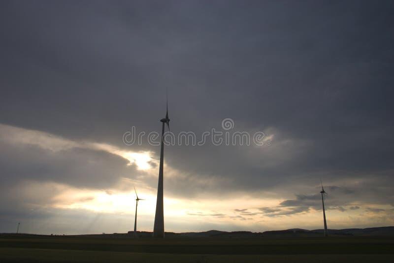Molinoes de viento en un día nublado en la puesta del sol foto de archivo libre de regalías