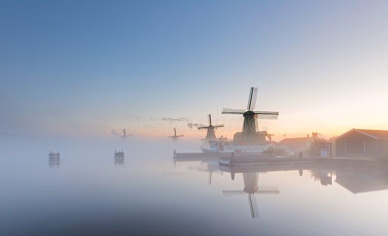 Molinoes de viento en una salida del sol de niebla en los Países Bajos foto de archivo libre de regalías