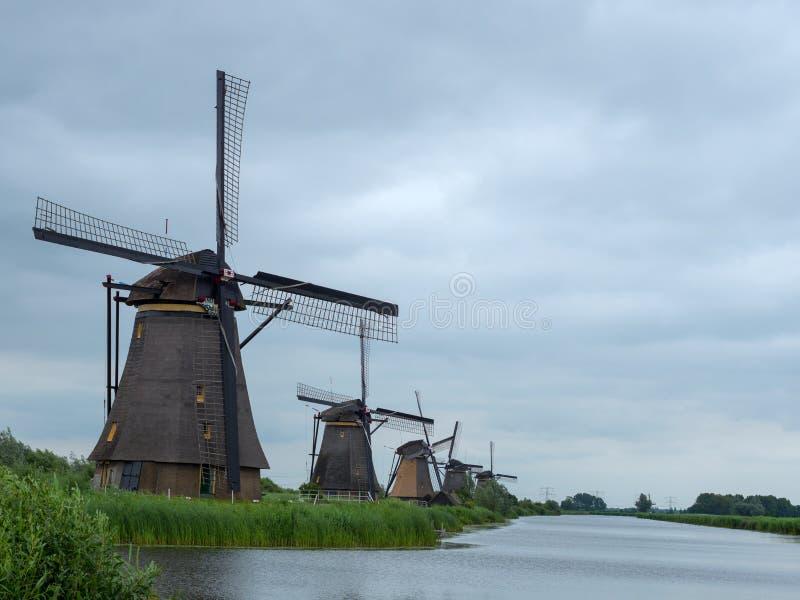 Molinoes de viento holandeses cerca del pequeño río en Kinderdijk imágenes de archivo libres de regalías