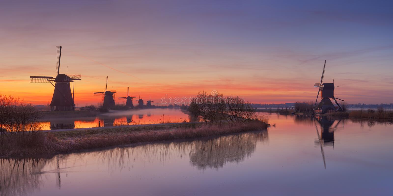 Molinoes de viento holandeses tradicionales en la salida del sol en el Kinderdijk foto de archivo libre de regalías