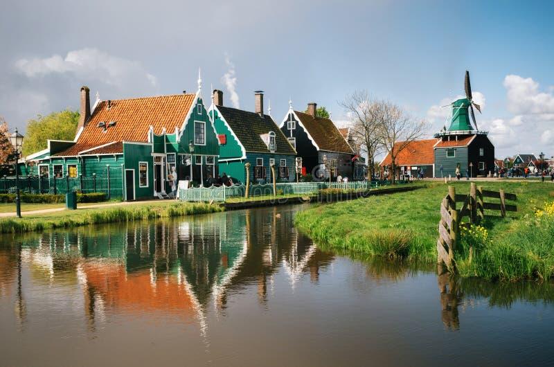 Molinos auténticos de Zaandam y casas vibrantes tradicionales en el canal del agua en el pueblo de Zaanstad, Países Bajos foto de archivo