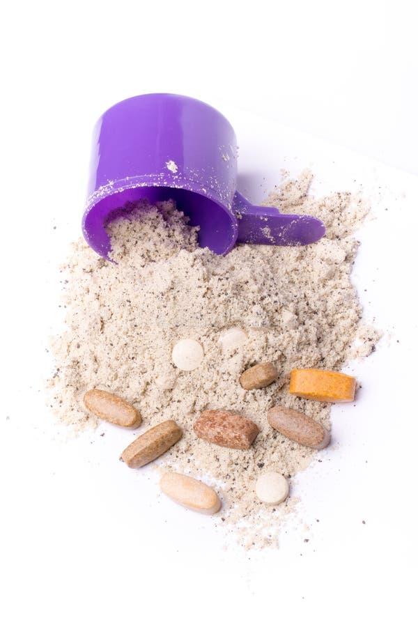 Molkeproteinpulver in der Schaufel mit Vitaminen und stockbilder