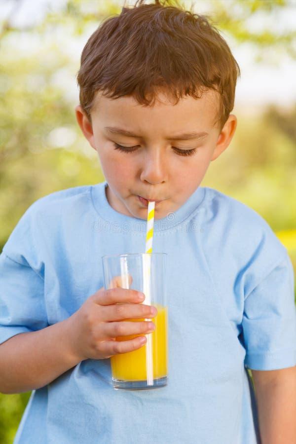 Molla all'aperto bevente della bevanda del succo d'arancia del ragazzino del bambino del bambino fotografie stock libere da diritti