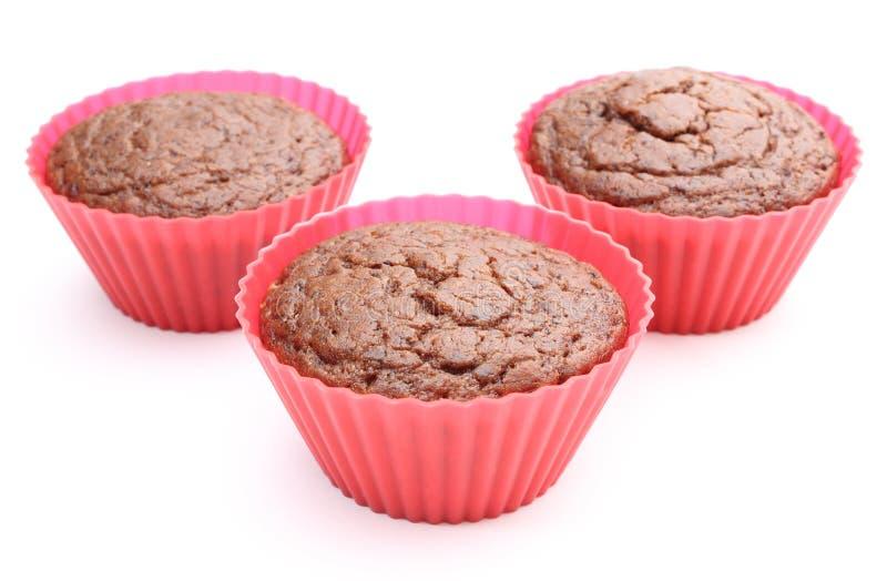 Mollete cocido fresco del chocolate en tazas rojas del silicón foto de archivo libre de regalías