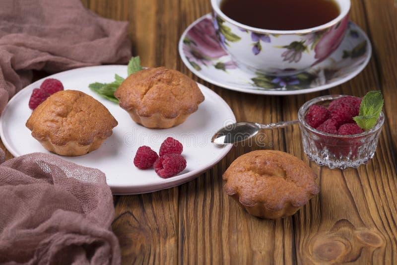 Mollete con las frambuesas y polvo del azúcar en la tabla con la tetera del té imágenes de archivo libres de regalías