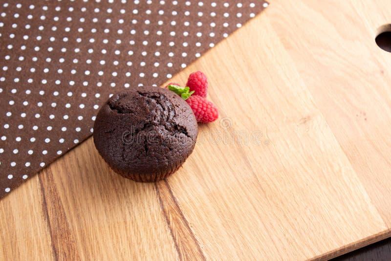 Mollete del chocolate con las bayas de la frambuesa en una tabla de madera ligera imagen de archivo libre de regalías