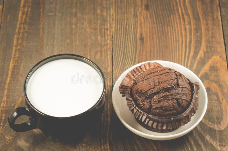 mollete del chocolate y mollete de la leche/del chocolate en una placa blanca y una taza negra con leche fotografía de archivo