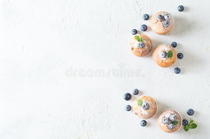Molletes o magdalenas de los arándanos con las hojas de menta en el textur blanco fotos de archivo libres de regalías