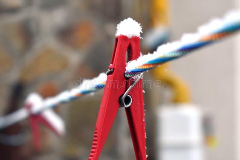 Molletta da bucato rossa innevata sulla linea variopinta, primo piano fotografia stock libera da diritti
