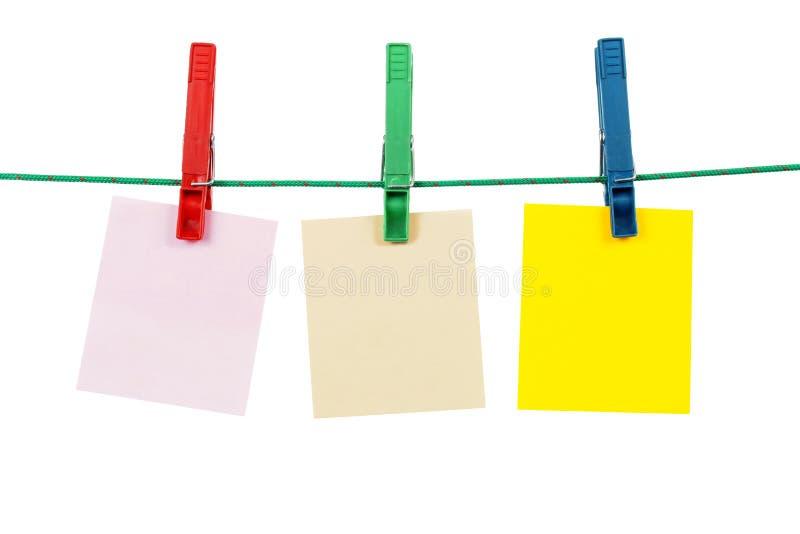 Mollette da bucato con le carte in bianco del messaggio fotografia stock libera da diritti