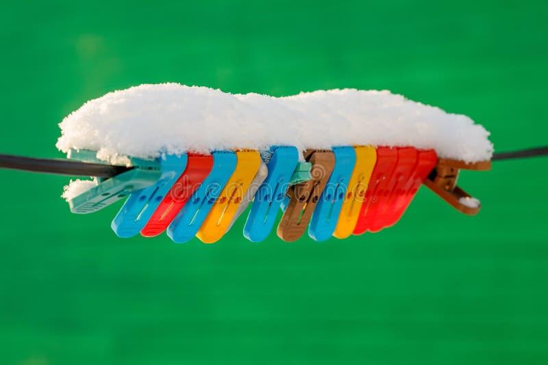 Mollette da bucato variopinte sulla corda da bucato coperta di neve all'aperto Scena di inverno fotografie stock libere da diritti
