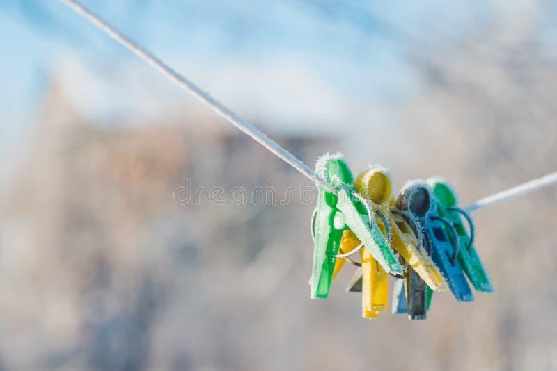 Mollette da bucato verdi, gialle e blu su una corda, coperta di brina di inverno fotografia stock