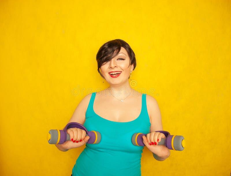 Mollig blij emotioneel meisje met kort haar in een blauwe t-shirt die sporten met domoren doen om gezond te zijn en gewicht op ge royalty-vrije stock foto